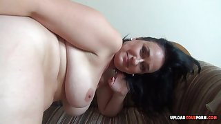 Astonishing mature with a big ass pleasures herself with a condom on her fingers.